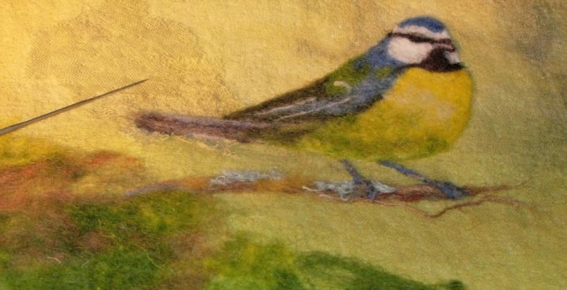 Needle-felt picture of a blue tit sitting on a branch.