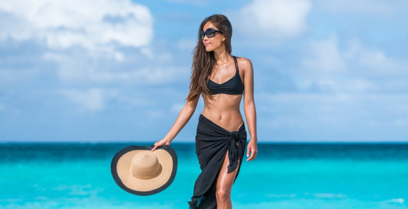 Make a Sarong. Image shows a woman on the beach wearing a Sarong skirt and crop top