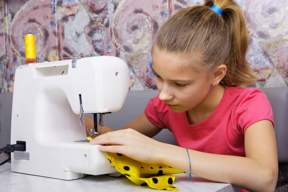 Kids sewing course. A young girls sits at a sewing machine using yellow spotted fabric