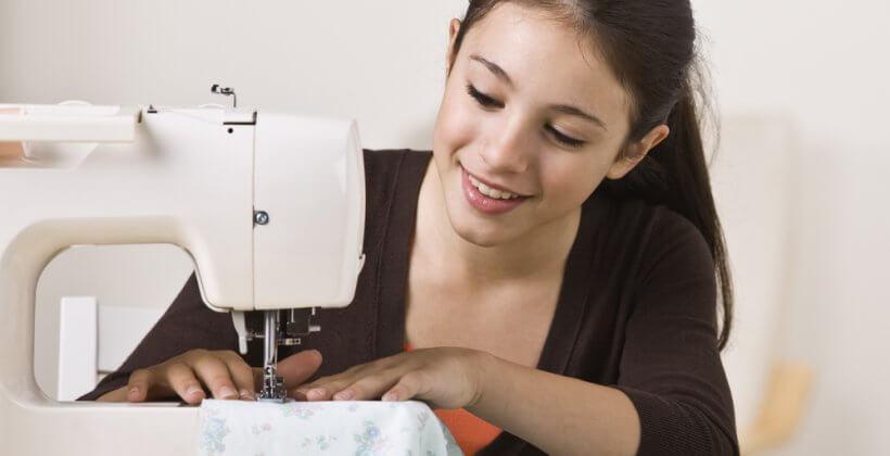 Kids learn to sew class - a young girl enjoying using her sewing machine