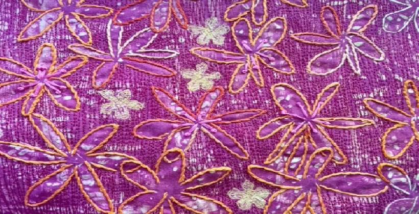 Monoprinted fabric with large daisy-like flowers which have been machine and hand embroidered