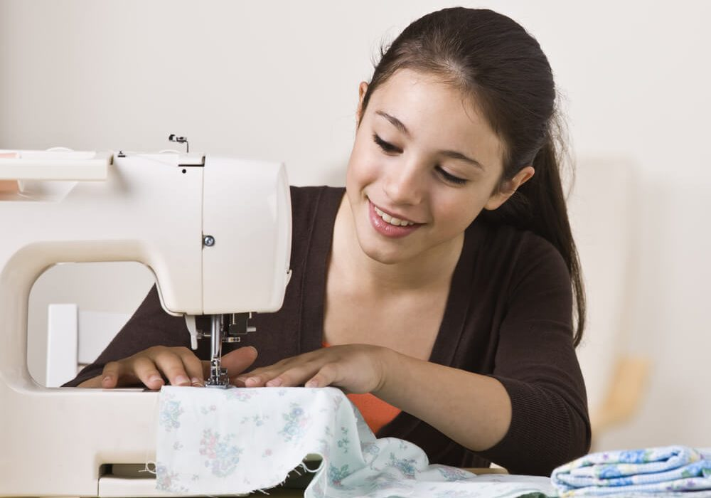 Kids introductory sewing class - a young girl enjoying using her sewing machine